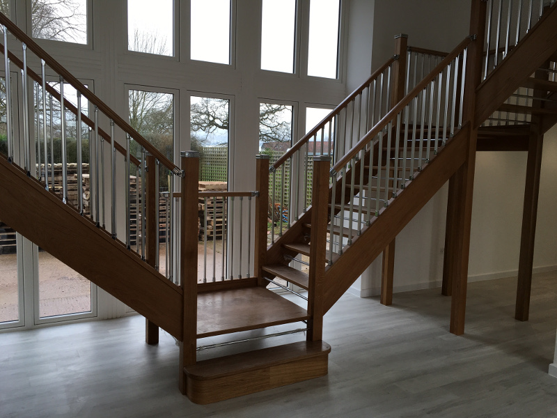 Oak open tread staircase with chrome riser rods. Chrome solution spindles with oak solution handrail and  handrail connectors. Oak newels with chrome solution caps