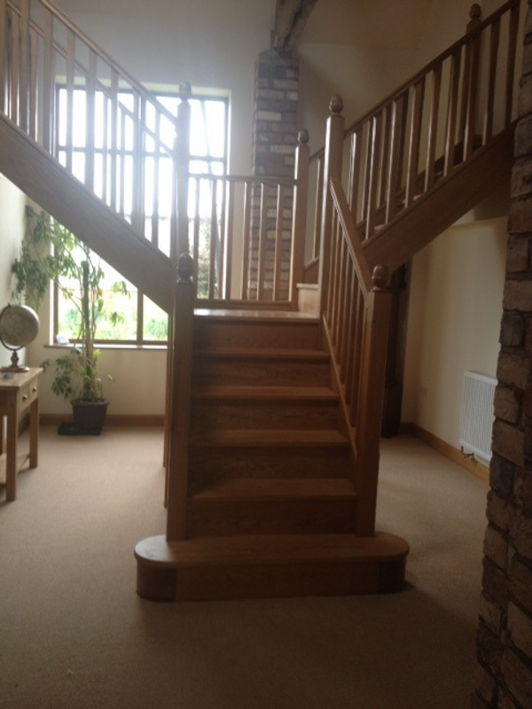 Oak staircase with double curtail to front, oak stop chamfered newels with acorns and 41mm oak stop chamfered spindles