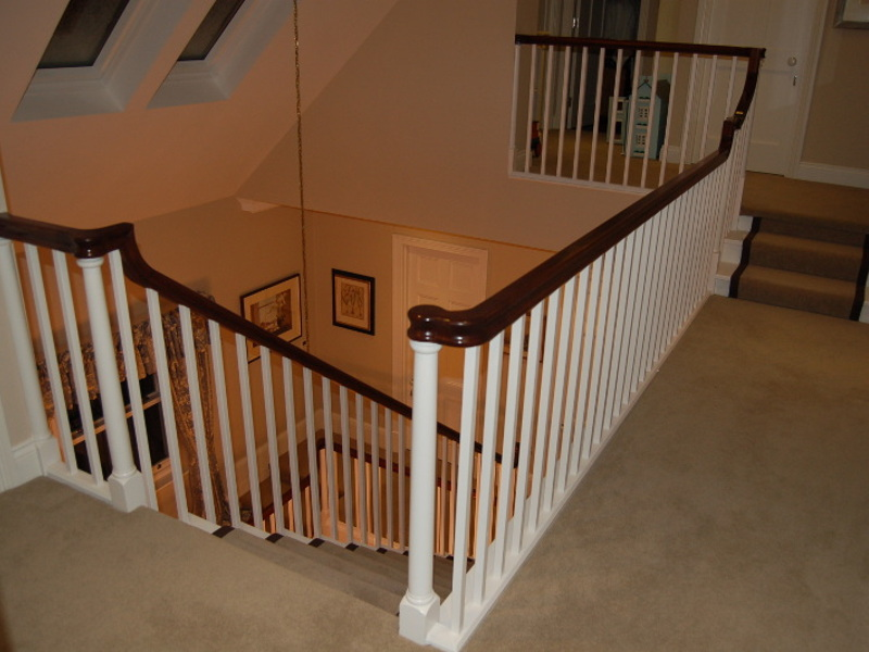 Sapele continuous handrail with bespoke turned newel posts and square spindles