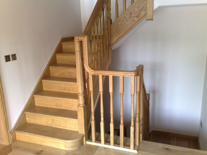 Oak staircase with fluted Georgian newel posts, oak continuous handrail and fluted Georgian spindles